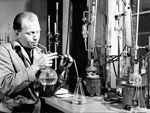 Chemist in a lab at the Sorel Steel plant draws liquid into a rounded, flat-bottomed glass jar to determine constituents of steel samples... / Un chimiste dans un laboratoire de l'aciérie Sorel Steel (Québec) pipette du liquide d'un erlenmeyer vers un bal