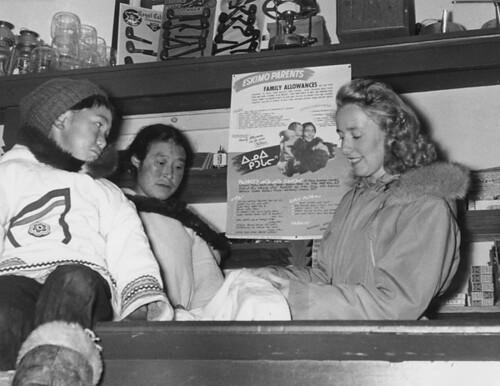 An Inuit boy sits on top of a counter as Mrs. Sigvaldasson serves an Inuit woman inside Sigvaldasson's store, Cape Smith, Smith Island, Nunavut / Un garçon inuit assis sur un comptoir pendant que Mme Sigvaldasson sert une Inuite dans le magasin Sigvaldass