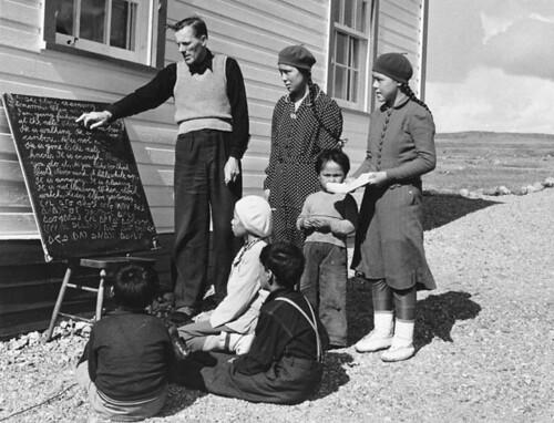 Anglican missionary Reverend W. James teaching his class of Inuit students how to read Inuktitut syllabics... / Le révérend W. James, missionnaire anglican, enseignant à sa classe d'étudiants inuits l'écriture syllabique de l'inuktitut...