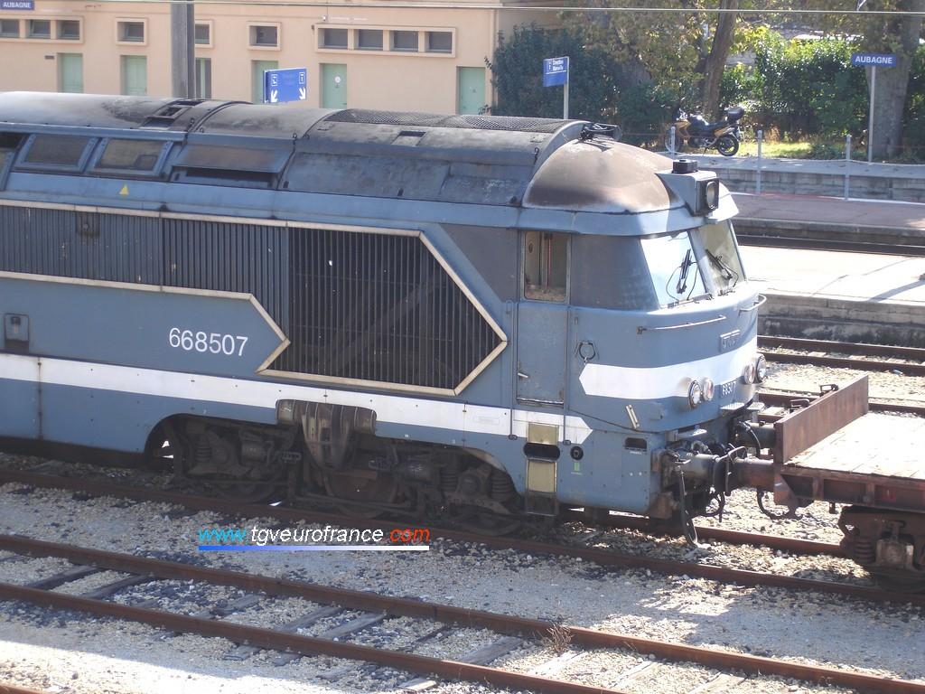 Une locomotive Diesel-électrique (A1A A1A  668507 de l'Infrastructure SNCF) à moteur AGO en livrée Arzens en tête d'un train de travaux à Aubagne