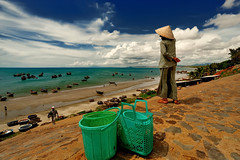 Waiting for fish (cteteris) Tags: sea sky woman beach wideangle vietnam baskets fishingboats fishingvillage muine 5photosaday nikkor20mm28 nikond700 idefinitlystalkedthiswoman ithinkshewastoobusywatchingtonoticeme ormaybeshewascursingmeunderherbreathinvietnamesehowamisupposedtoknow