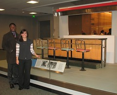 Two young people in front of a museum display of a section of 50's-style lunch counter with four seats.