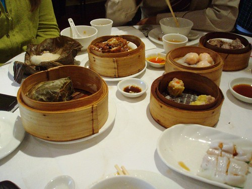 A large table covered with a white tablecloth and with several dishes and steamer baskets arranged on top.  The steamers contain rice in lotus leaf, siu mai, har gao, and suchlike items.  A dish of cheung fun is in the foreground, and saucers of various dipping sauces sit between the steamers.