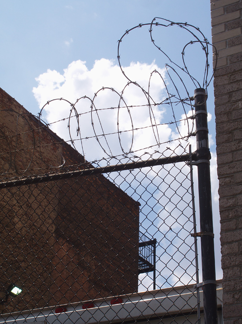 razor wire tops a fence in Manhattan, with clouds in the background, NYC