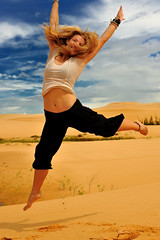 Spread your wings and fly (cteteris) Tags: portrait fly jump desert tamara happiness 50mm14 vietnam sanddunes muine 5photosaday gravitysucks nikond700 thefactthatherrighthandiscutoffisdrivingmeabsolutlynutsbutiloveherhairandtherestoftheframingsoicouldntresistpostingit
