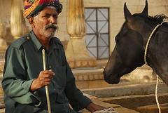 I have my eyes on you. Stable head at Mandir Palace (sanjayausta) Tags: horse india man black heritage history look walking town asia with dress indian traditional small palace stick turban stern stable jaisalmer mandir sanjay rajasthan gaurd rajasthani hourse austa