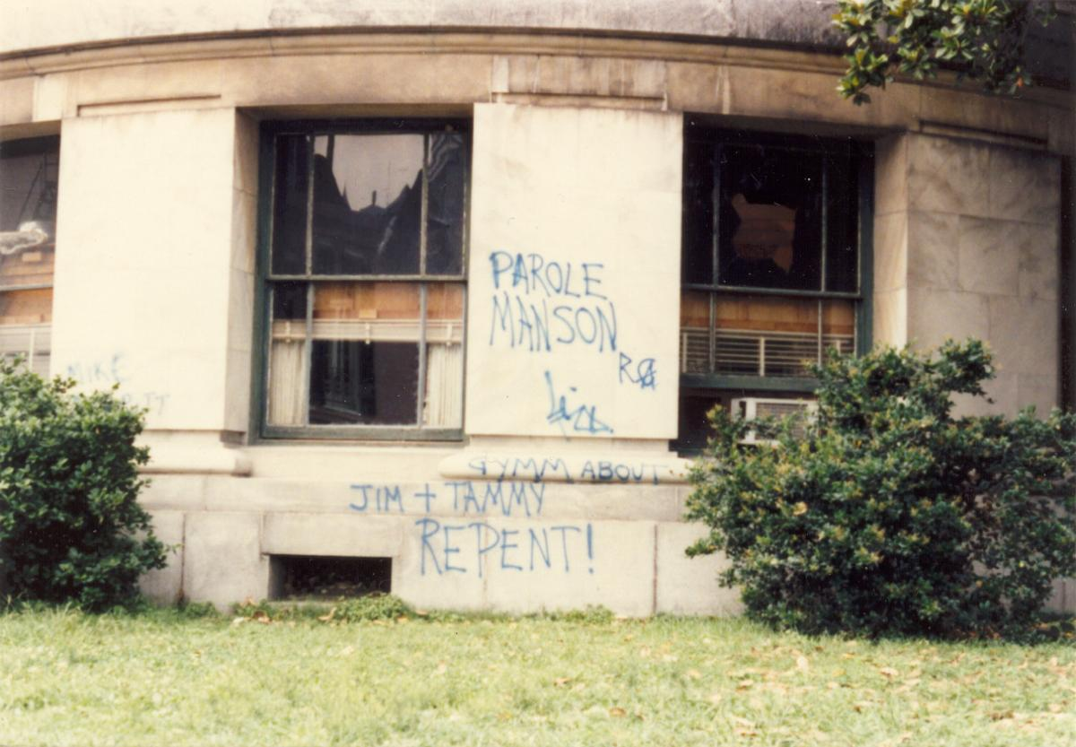 abandoned building somewhere in New Orleans with graffiti to Parole [Charles] Manson and for Jim and Tammy Bakker to repent!
