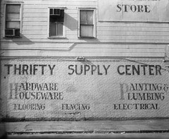 Sign Of The Times (evanleavitt) Tags: county camera windows light bw history film sign analog speed america ga vintage georgia town hardware store graphic south details small bricks ghost large advertisement southern chatham american americana weathered 4x5 format savannah fading timeless graflex the of