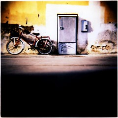Fat Bottomed Girls They'll Be Riding Today (ale2000) Tags: street urban muro bicycle yellow stone wall race wow mediumformat square concrete holga xpro strada cross floor kodak crossprocess wheels queen photowalk bici process epp vignetting bicicletta pavimento ruote fatbottomedgirls electricitybox mrqueen centralina aledigangicom cronacheurbane