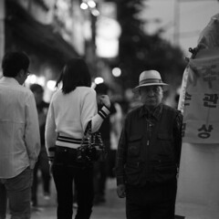the fortune teller (memetic) Tags: street bw man 6x6 hat blackwhite bokeh south korea tent seoul hp5 fortuneteller jongno passerby  arax60