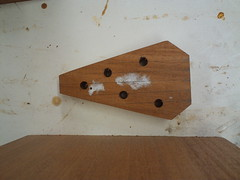 The peg holes are perpendicular to the surface of the peghead.