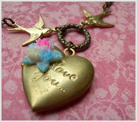 "Two birds in love, carrying a beautiful old brass locket with ""Love You"""