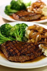Sirloin steak with mashed potatoes with mushroom and onion topping and broccoli