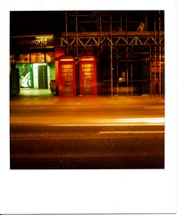 Isolation (Lady Vervaine) Tags: sf road street city uk longexposure light red england urban cinema black green london public publicspace night booth dark scaffolding glow phone darkness box britain phonebooth empty telephone doctorwho joydivision glowing isolation sciencefiction drwho lighttrails cinematic emptiness telephonebox phonebox telephonebooth publicphone lighttrail polaroidsx70 cineworld