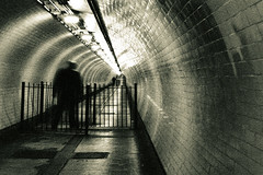 Woolwich tunnel (Che-burashka) Tags: longexposure light man london monochrome underground walking person 50mm tube grain tunnel spooky human tunnels gettys tgif woolwich slowshutterspeed skifi xoxoxox 400d underthethames blurpeople otherlondon locallondon diminishingpoint katianosenko thrillerillustration
