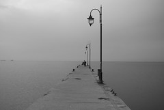 why so lonely? (andreas n) Tags: sea sky people blackandwhite bw sun white black love beach lamp kids blackwhite dock nikon flickr loneliness afternoon walk hellas happiness explore greece nostalgia thoughts grecia thessaloniki lonely seafront griechenland grce soe salonica firstquality peraia abigfave platinumphoto diamondclassphotographer d40x  ysplix artlegacy