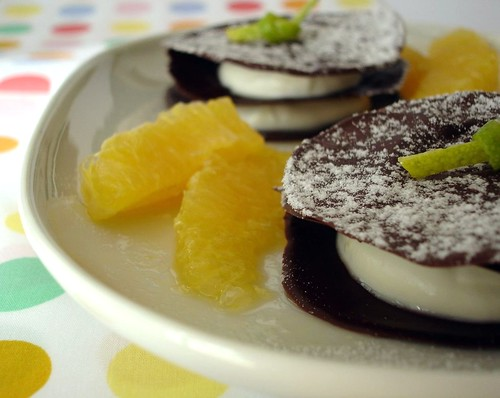 Chocolate discs with orange cream and marinated oranges