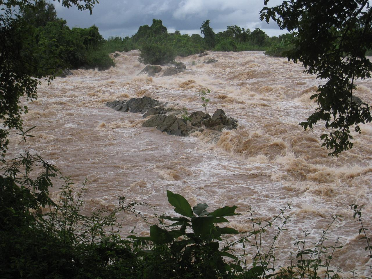 A large waterfall rages alongside the island of Don Khone.