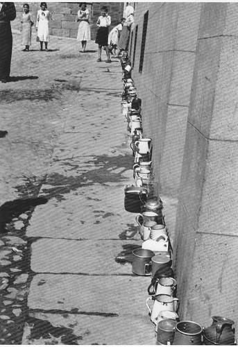 Población civil esperando abastecimiento en la Calle de la Ciudad junto a la fuente del ayuntamiento (Toledo) en la Guerra Civil. Septiembre de 1936. Fotografía de Hans Namuth/Georg Reisner