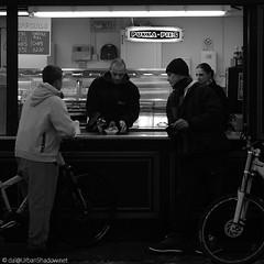 Pukka (Clockwork Noggin) Tags: uk bw man boys monochrome counter candid norfolk streetphotography bikes greatyarmouth serving chipshop fishandchips marineparade pukkapies blackwhitephotos canoneos400d clockworknoggin yarmouthflickrmeet