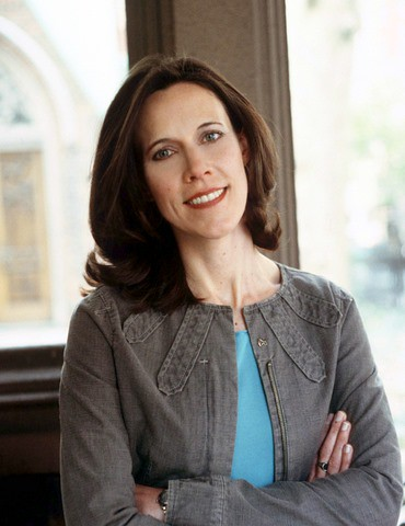 Author Megan McCafferty, who has shoulder-length brown hair, smiles in front of a lighted window with her arms crossed, wearing a teal-colored top and a grey jacket.