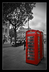 Phone boxes (Roger.C) Tags: old red england bw colour london monochrome strand canon shadows phone telephone trafalgar sigma historic chapeau boxes vignette selective 30d 1770mm mywinners diamondclassphotographer flickrdiamond
