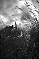 windy_church.jpg (gitdwon) Tags: sky urban bw white storm black church grass clouds canon dark wind religion perspective slovenia dslr maribor