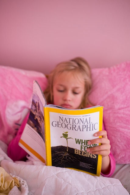 girl reading National Geographic in bed