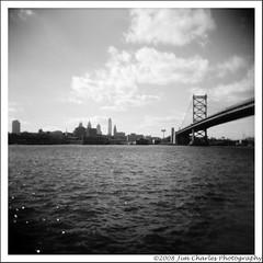 Ben Franklin Bridge and Philadelphia Skyline (Jim Charles Photography) Tags: bridge bw black film philadelphia water skyline architecture river holga camden philly delaware benfranklinbridge benfranklin ilford ilforddelta100