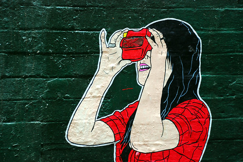 young woman/girl in a red tshirt looking through a view master toy