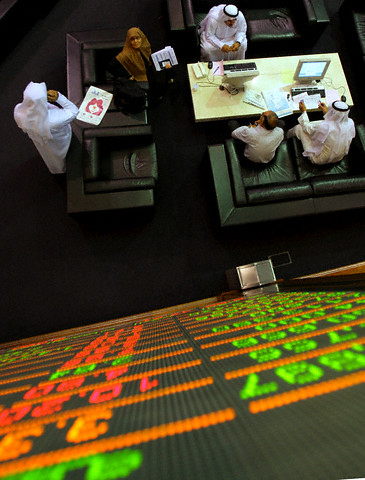 UAE Traders watch an electronic quotation board at the stock exchange in Dubai Financial Marke
