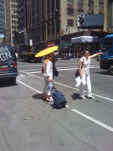 Two ladies on the streets of New York with a yellow parasol - Taken With An iPhone