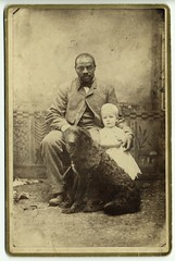 Black man with white child and dog.