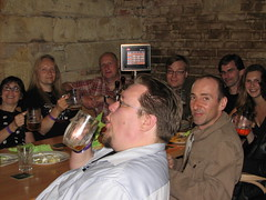 9 persons crammed around a pub table, toasting with their beers