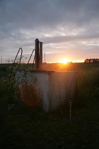 Metallbottich unter freiem Himmel im Sonnenuntergand