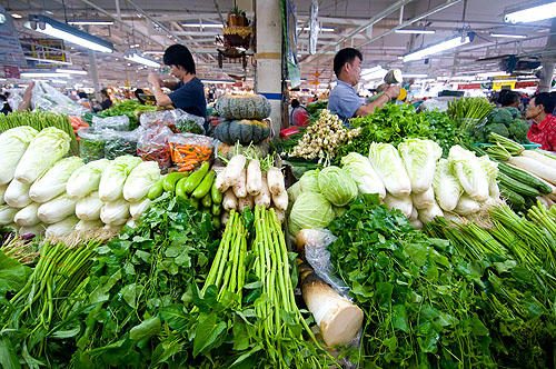 Two vendors selling vegetables at Bangkok's Or Tor Kor Market