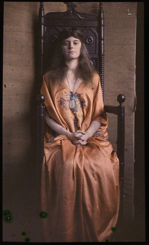 Woman in Oriental inspired gown, sitting in wooden throne, c. 1915, by Unknown photographer, color p