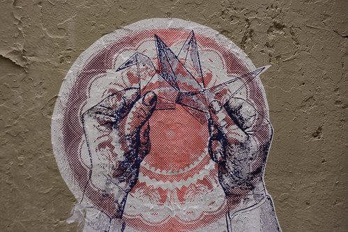 graffiti poster -- the white outline of hands folding an origami crane; behind the drawing is a red and white mandala