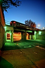 Stopped at the Amshack (Mark Branly) Tags: road city blue trees light sky urban orange green night train canon dark concrete evening nc cityscape durham steel tracks overpass northcarolina flourescent dslr asphault amtrack amshack