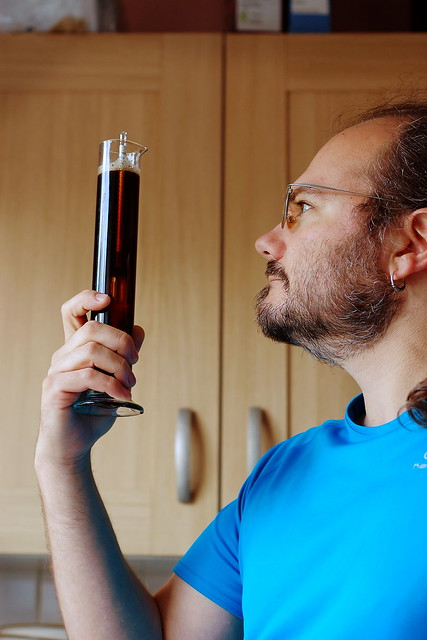 Wulf standing in front of a window holding up a sample tube of beer