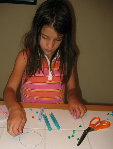 Stringing her clothespins and beads together
