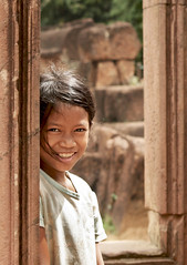 Windowed smile - Banteay Srei - Cambodia (Christophe Paquignon) Tags: world pictures voyage trip travel portrait color colors girl smile face canon temple photography eos photo ruins cambodge cambodia gesicht foto faces image little photos pics couleurs picture images du adventure round around christophe angkor monde 2008 backpacker amateur pict fille sourire autour couleur petite visage ruines aventure banteay srei visages 50d 400d flickrchallengewinner kryyslee christophepaquignon paquignon