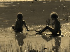 """To myself I am only a child playing on the beach, while vast oceans of truth lie undiscovered before me."" (stjernesol) Tags: light sea summer beach water norway sepia reflections children norge shades wonderfultimes sittinginwater being4yearsold"