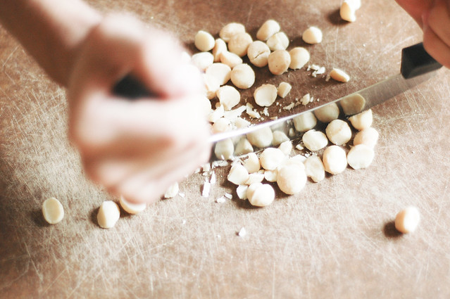 macadamia nuts being chopped with a mezzaluna