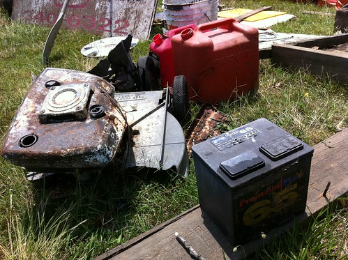 A lawnmower, gas cans and a car battery