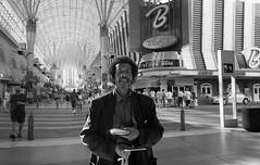 Binions (LoFiKen) Tags: people urban bw guy film set walking person blackwhite holding walkman lasvegas head cd streetphotography fremont headsets 123bw candidblackwhite