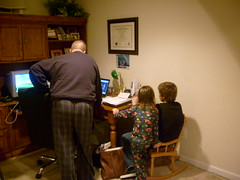 Powell, Thomas, Pie, and Dad Gathered Around the Computer