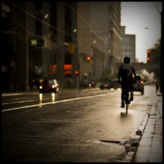 Westbound (Js) Tags: street light toronto wet rain silhouette lights evening cyclist dof bokeh pavement 85mm drain manhole asphalt vignette bycicle queenstwest 85mmf18d