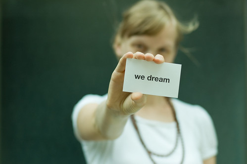A girl holding a paper that says we dream