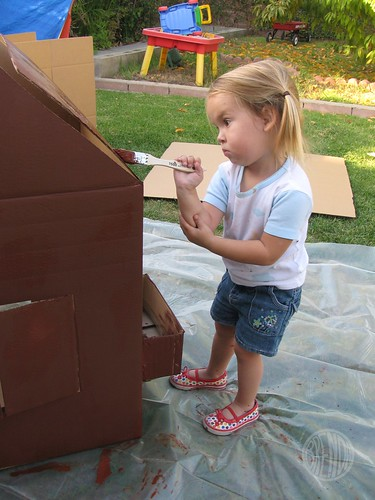 a little girl painting cardboard gingerbread house